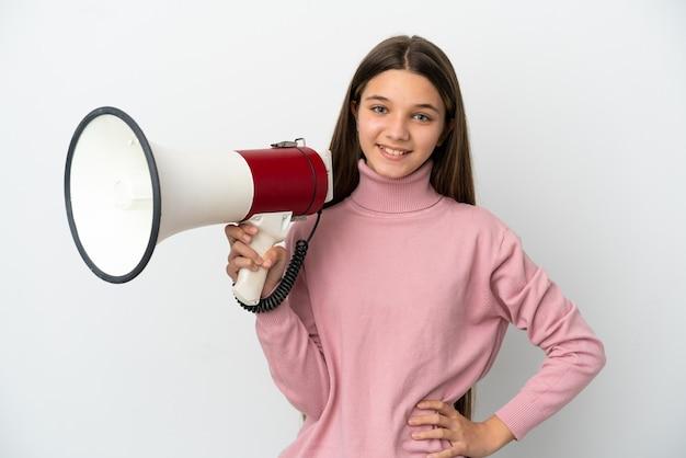 Маленькая девочка на изолированном белом фоне держит мегафон и улыбается