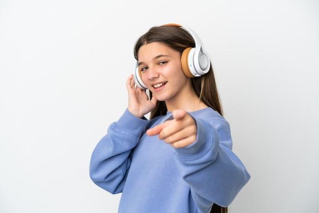 孤立した白い背景の上の少女が音楽を聴き、正面を指しています