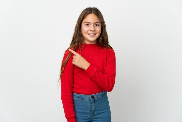 Маленькая девочка на изолированном белом фоне, указывая в сторону, чтобы представить продукт