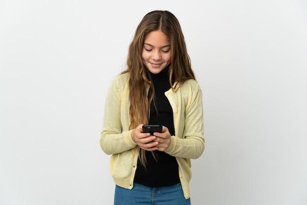 Маленькая девочка на изолированном белом фоне, отправив сообщение с мобильного телефона