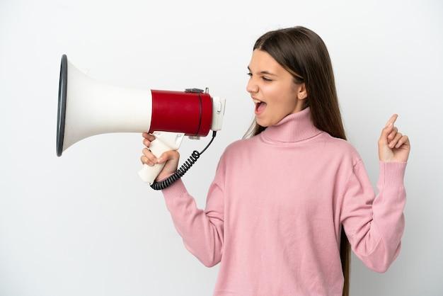 Маленькая девочка на изолированном белом фоне кричит в мегафон, чтобы объявить что-то в боковом положении
