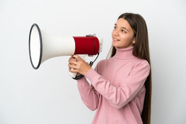 Маленькая девочка на изолированном белом фоне кричит в мегафон, чтобы что-то объявить