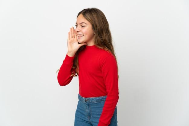 Маленькая девочка на изолированном белом фоне кричит с широко открытым ртом в сторону