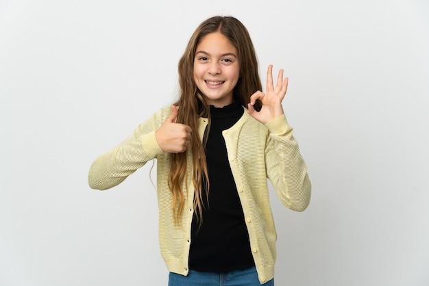 확인 서명 및 엄지 제스처를 보여주는 격리 된 흰색 배경 위에 어린 소녀