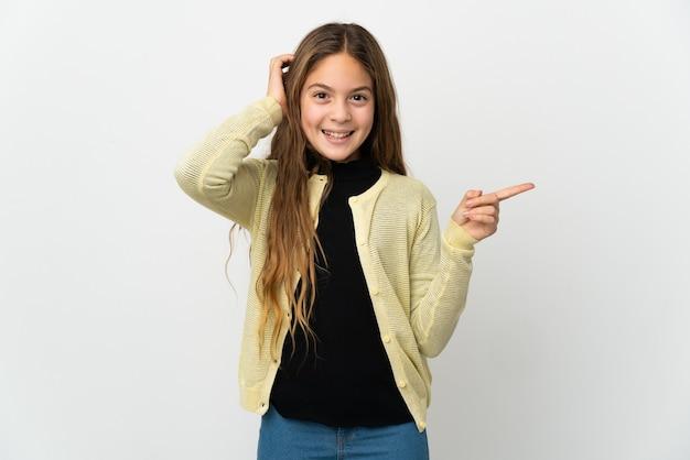 Маленькая девочка на изолированном белом фоне удивлена и указывает пальцем в сторону