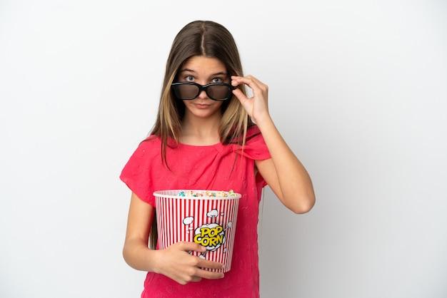 고립된 흰색 배경 위에 있는 어린 소녀는 3d 안경에 놀라고 큰 팝콘 양동이를 들고 있다