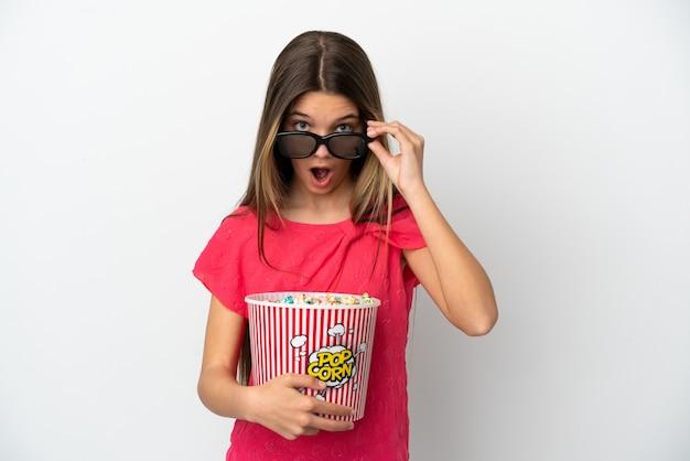Маленькая девочка на изолированном белом фоне удивлена 3d-очками и держит большое ведро попкорна