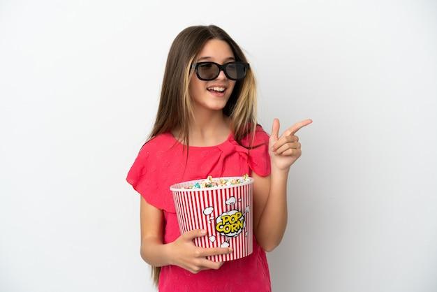 고립된 흰색 배경 위에 3d 안경을 쓰고 앞을 가리키는 동안 큰 팝콘 양동이를 들고 있는 어린 소녀
