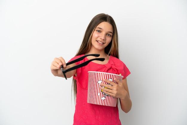 격리된 흰색 배경 위에 3d 안경을 쓰고 큰 팝콘 양동이를 들고 있는 어린 소녀