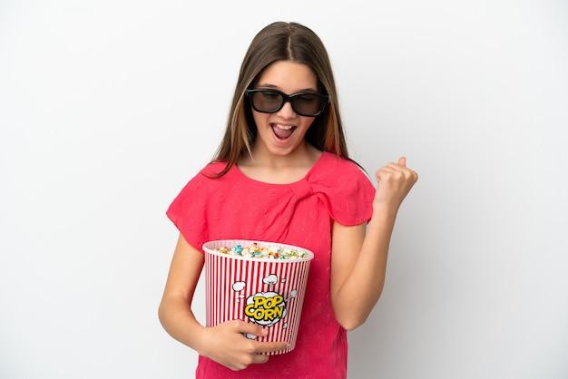 Маленькая девочка на изолированном белом фоне в 3d-очках и держит большое ведро попкорна