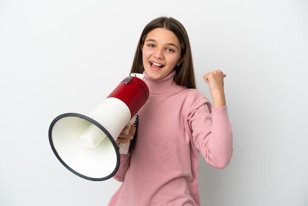 Маленькая девочка над изолированной белой стеной кричит в мегафон и указывает сторону