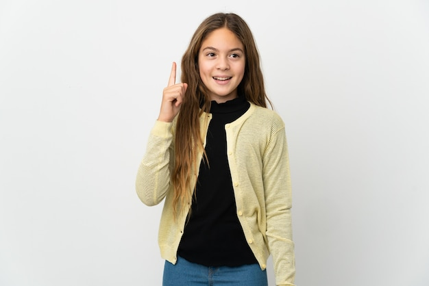 손가락을 가리키는 아이디어를 생각하는 고립 된 흰 벽 위에 어린 소녀