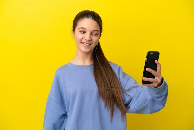 Маленькая девочка на изолированном желтом фоне, делая селфи с мобильным телефоном