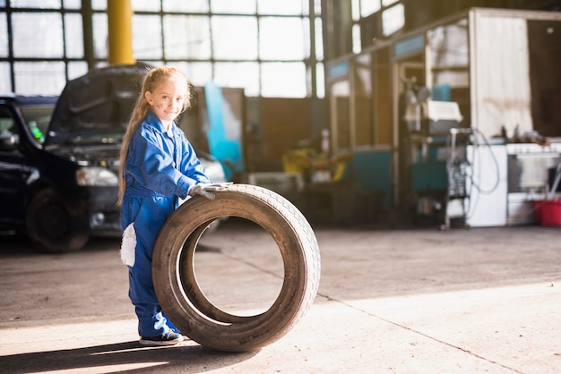 Little girl in overall standing with car wheel