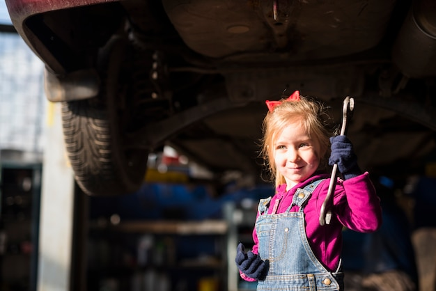 Little girl in overall standing with spanner