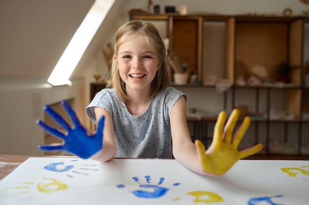 Маленькая девочка нарисовала руки гуашью
