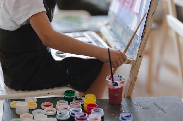 스튜디오나 미술 학교에서 그림을 그리는 어린 소녀. 창의적인 생각에 잠긴 화가 아이는 워크샵에서 캔버스에 다채로운 그림을 그립니다.