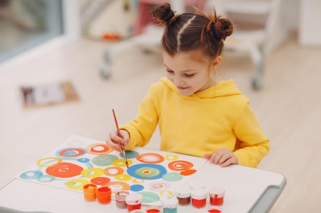 Маленькая девочка рисует художественную картину в помещении детский сад домашний стол кистью и акварельными красками