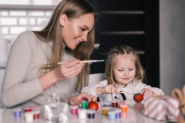 Little girl painting easter eggs with mother in the kitchen