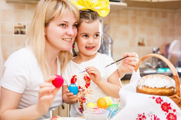 Little girl painting easter eggs with mother