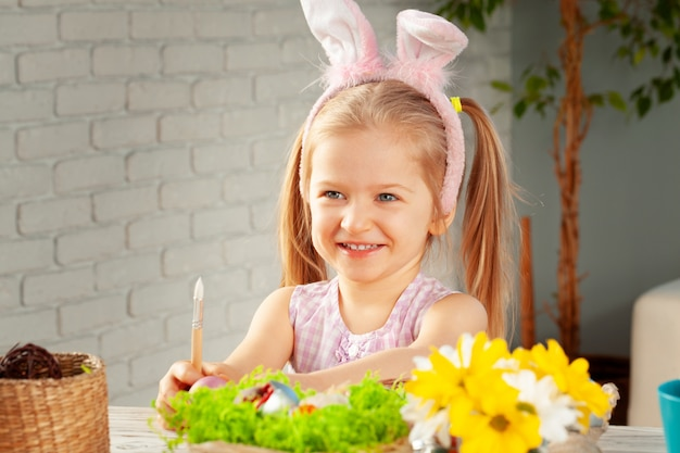 Little girl painting eggs for easter at home