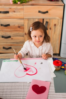 Little girl painting heart on paper