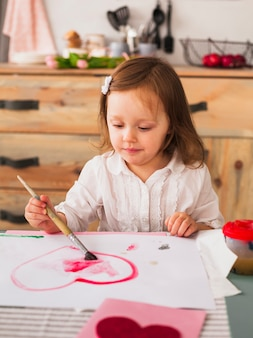 Little girl painting red heart on paper