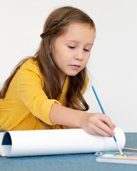 Маленькая девочка рисует с помощью палитры