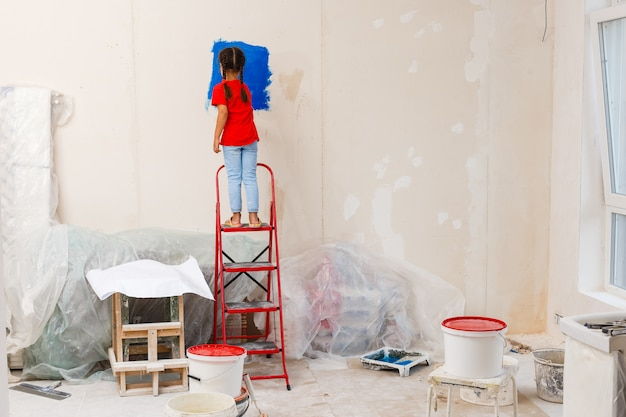 Little girl painting a wall at home