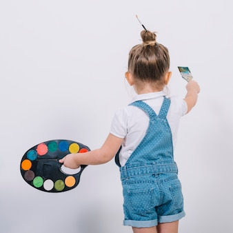 Little girl painting wall with brush