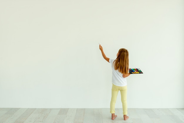 Little girl painting on white wall indoors