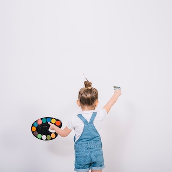 Little girl painting white wall with brush
