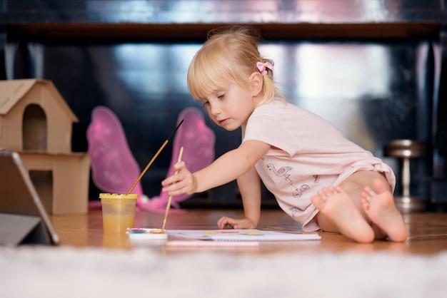 Маленькая девочка рисует кистью
