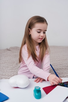 Little girl painting with a brush