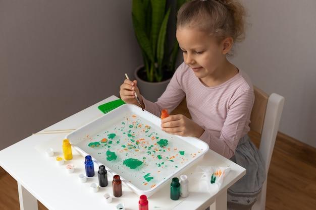 テーブルに座って、エブルの絵の具で絵を描く少女