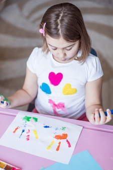 Little girl painting with her hands and fingers at home
