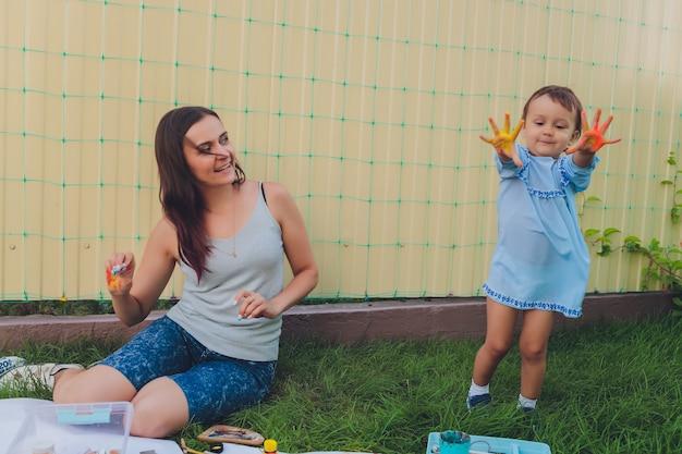 Маленькая девочка рисует с матерью на заднем дворе