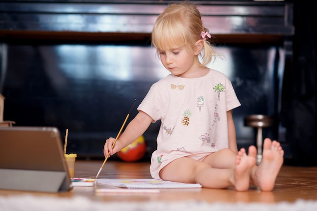 Little girl painting with a paintbrush