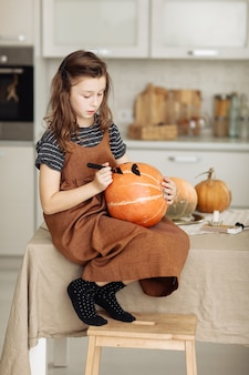Маленькая девочка рисует тыкву для подготовки к хеллоуину
