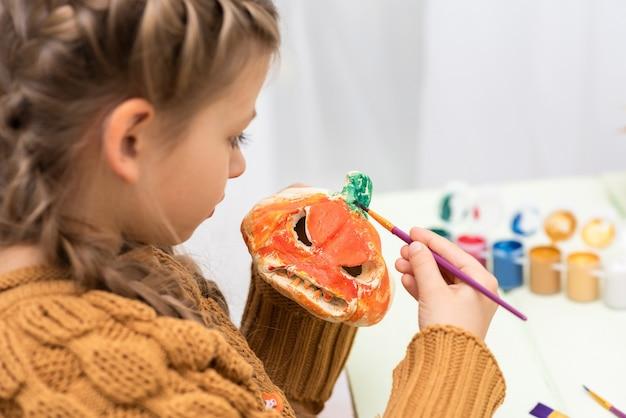 Маленькая девочка рисует тыкву цветами.