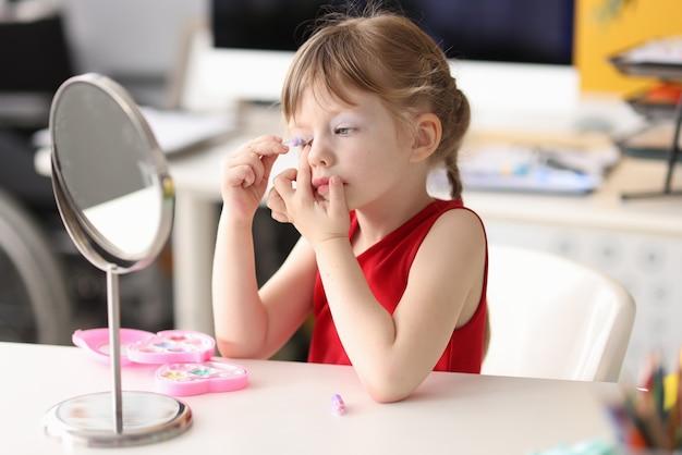 小さな女の子は彼女の目をペイントし、鏡で見る