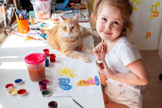 A little girl paints the sun and her mother with watercolors a ginger cat lies next to the table.