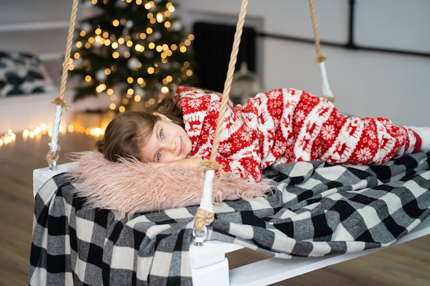 A little girl in pajamas can't sleep on a festive night.