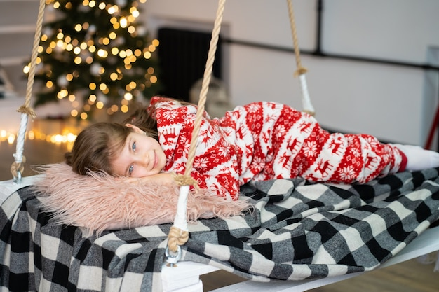 A little girl in pajamas can't sleep on a festive night