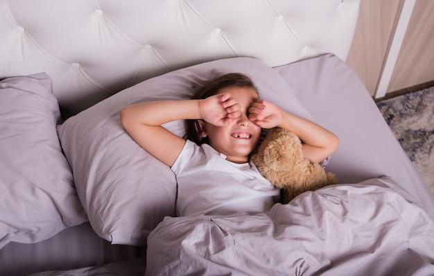 A little girl in pajamas sleeps in a crib with a teddy bear
