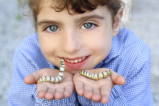 Little girl palying with silkworm in hands
