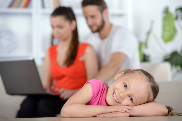 Little girl on a of parents using laptop.