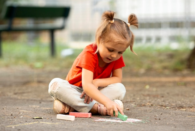 Little girl in park drawing with chalk