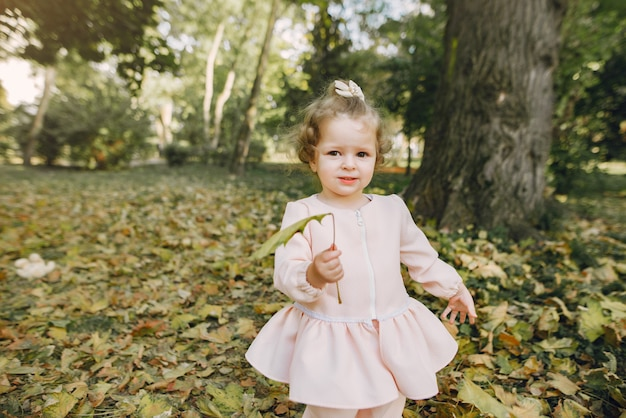 Little girl in a park in a pink dress playing