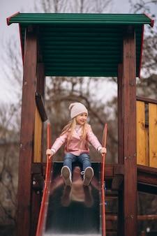 Little girl in park on a slide